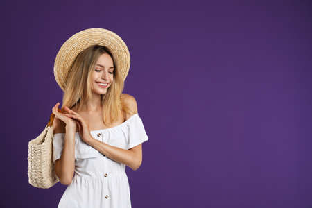 Beautiful young woman with stylish straw bag on purple background. Space for text