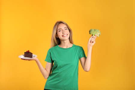 Woman choosing between cake and healthy broccoli on yellow background 版權商用圖片