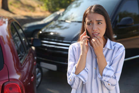 Stressed woman talking on phone after car accident outdoors