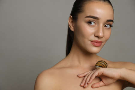 Beautiful young woman with snail on her hand against grey background. Space for text
