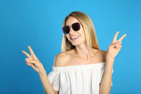 Beautiful woman in stylish sunglasses on light blue background 版權商用圖片