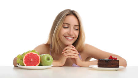 Woman choosing between cake and healthy fruits at table on white background 版權商用圖片