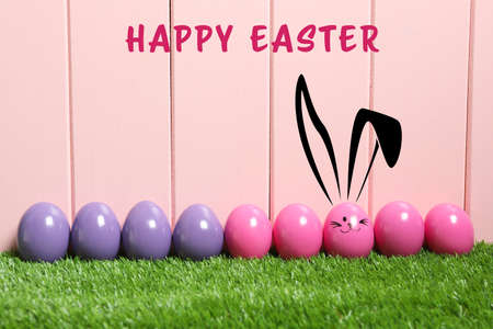 One egg with drawn face and ears as Easter bunny among others on green grass against pink wooden background