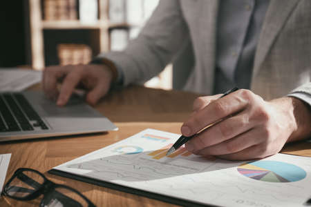 Businessman working with charts and graphs at table in office, closeup. Investment analysis