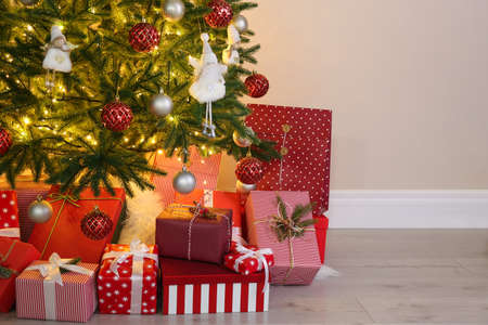 Pile of gift boxes near Christmas tree indoors