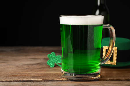 Green beer and St Patrick's Day decor on wooden table against black background. Space for text