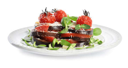 Baked eggplant with tomatoes, cheese and basil in plate isolated on white