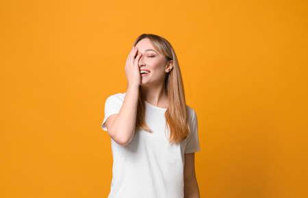 Beautiful young woman laughing on yellow background. Funny joke Stock Photo