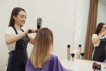 Stylist drying client's hair in beauty salon