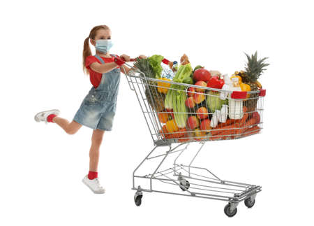 Little girl in medical mask with shopping cart full of groceries on white background
