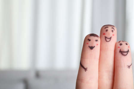 Three fingers with drawings of happy faces on blurred background, space for text