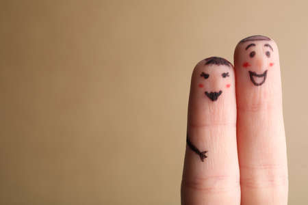 Two fingers with drawings of happy faces on brown background, space for text. Spending time together Imagens