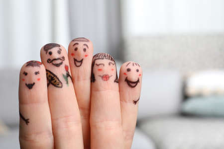 Five fingers with drawings of happy faces on blurred background