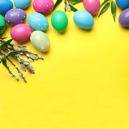 Bright painted eggs and pussy willows on yellow background, flat lay with space for text. Happy Easter