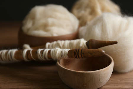 Spindles and soft white wool on wooden table, closeup