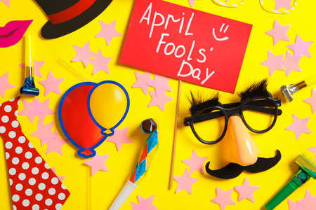 Sign with phrase April Fools' Day and different clown's accessories on yellow background, flat lay