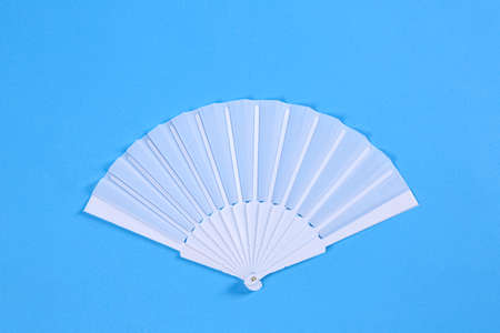 White hand fan on light blue background, top view