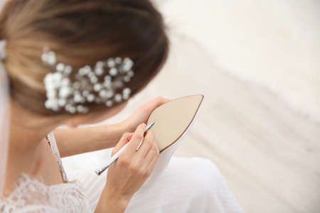 Young bride writing on her shoe indoors, above view. Wedding superstition