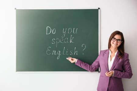 Teacher near green chalkboard with words Do You Speak English?