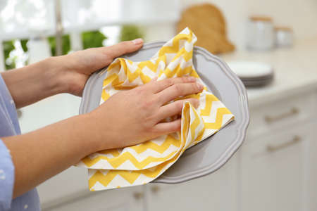 Woman wiping plate with towel in kitchen, closeup Reklamní fotografie