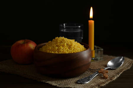 Millet, apple, water, burning candle and crucifix on wooden table. Great Lent season