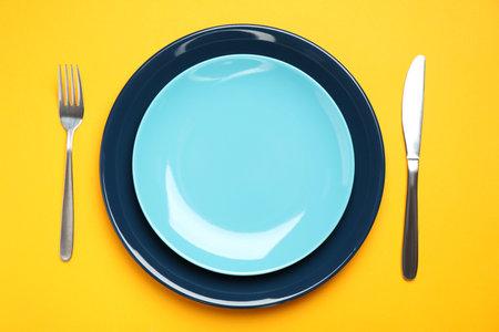 Stylish table setting on orange background, flat lay