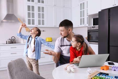 Children disturbing stressed man in kitchen. Working from home during quarantine Stockfoto