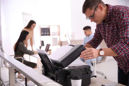 Employee using new modern printer in office Stock Photo