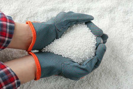 Farmer holding ammonium nitrate pellets in hands over pile, top view. Mineral fertilizer Imagens