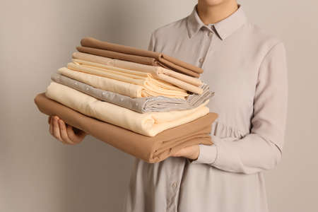 Woman holding stack of clean bed linens on beige background