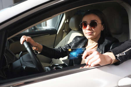 Woman sitting in car and giving credit card at gas station Banco de Imagens