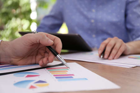 Business people working with charts and graphs at table in office, closeup. Investment analysis