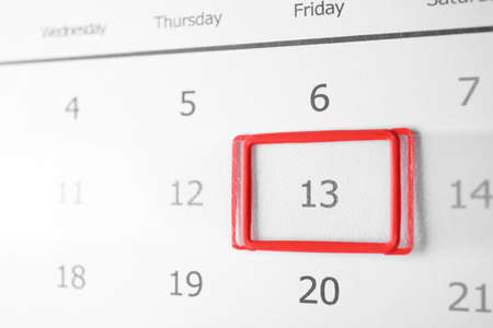 Closeup view of calendar page, focus on Friday 13. Bad luck superstition