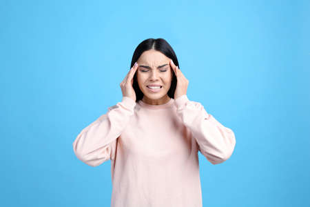 Portrait of stressed young woman on light blue background Stock Photo