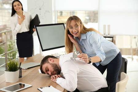 Young woman sticking paper fish to colleague's back while he sleeping in office. Funny joke