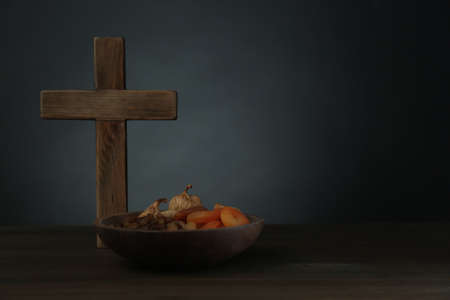 Cross and dried fruits on wooden table, space for text. Lent season