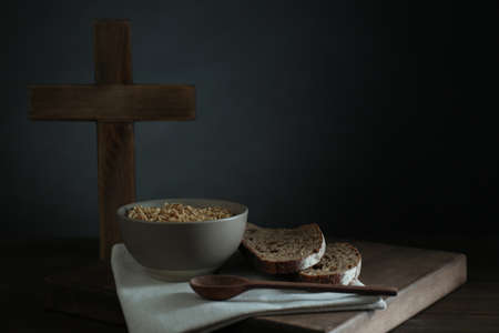 Oatmeal porridge, bread and cross on wooden table, space for text. Lent season