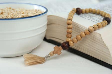 Oatmeal, rosary beads and Bible on white table, closeup. Lent season