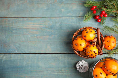 Flat lay composition with pomander balls made of fresh tangerines and cloves on wooden table, space for text