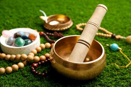 Composition with golden singing bowl on green grass, closeup. Sound healing Stock fotó