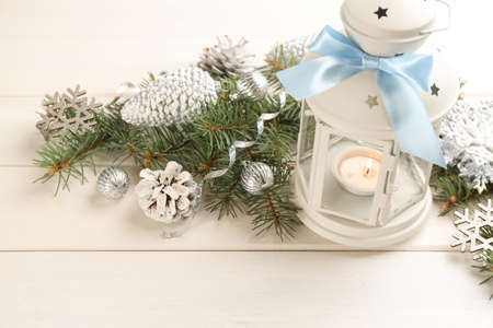 Christmas lantern with burning candle and festive decor on white wooden table