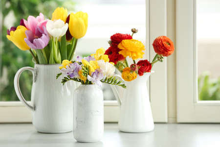 Different beautiful spring flowers on window sill Stockfoto