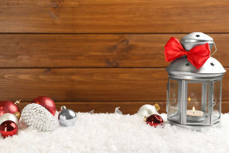 Christmas lantern with burning candle and festive decor on snow. Space for text 版權商用圖片