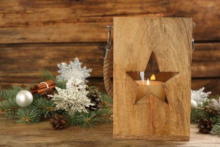 Christmas lantern with burning candle and festive decor on wooden table. Space for text