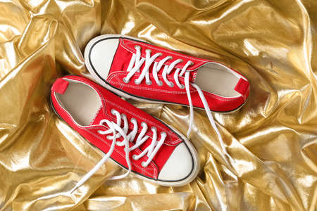 Pair of stylish shoes with laces on gold fabric, flat lay Standard-Bild