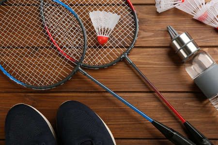 Rackets, sportswear and bottle on wooden table, flat lay. Playing badminton