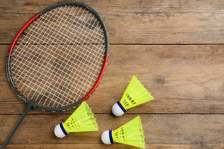Racket and shuttlecocks on wooden table, flat lay with space for text. Badminton equipment
