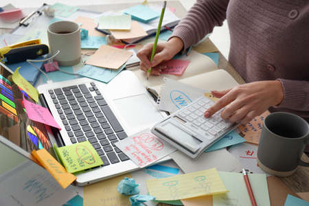 Overwhelmed woman working at messy office desk, closeup Imagens