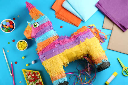 Flat lay composition with cardboard donkey and materials on blue background. Pinata diy