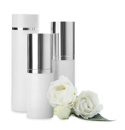 Different cosmetic products and fresh flowers on white background